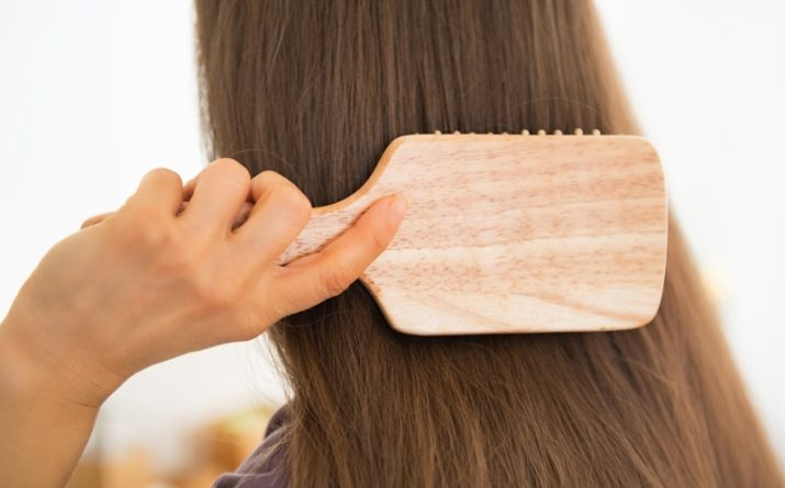 girl with long hair is combing it