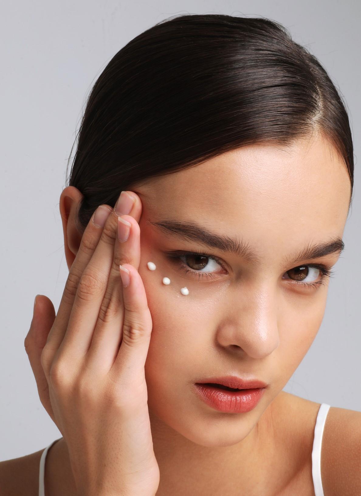 woman is applying an under-eye cream